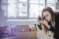 Architect taking photo of architectural model in office - GUSF00598