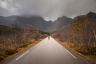 Norway, Lofoten Islands, man standing on empty road surrounded by rock face - WVF00945