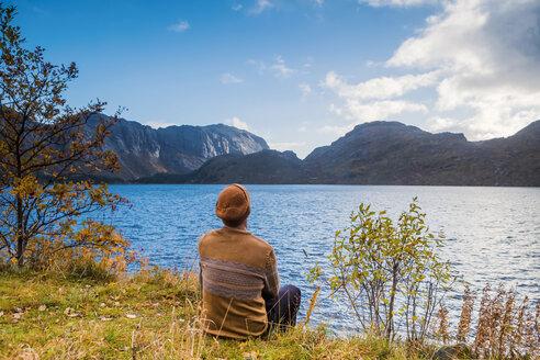 Norway, Lofoten Islands, Storvand, man sitting at the seashore - WVF00948