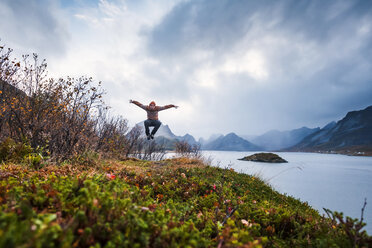 Norway, Lofoten Islands, man jumping at the coast - WVF00960