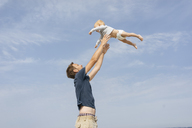 Germany, Timmendorfer Strand,  Father throwing son in the air - KNSF03687