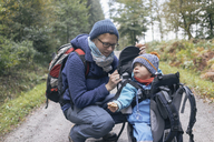 Son eating bread, sitting in his back-basket, next to his mother during hiking - KNSF03690