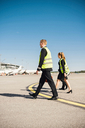 Full length of cabin crew walking at airport against clear blue sky - MASF00003