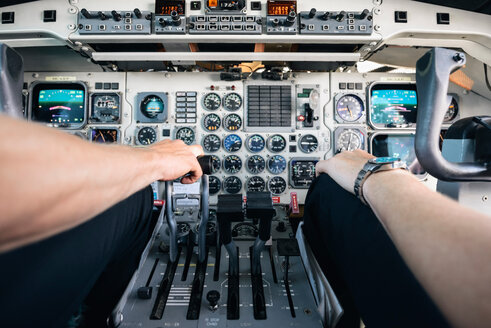 Cropped image of pilots sitting by control panel in cockpit - MASF00006