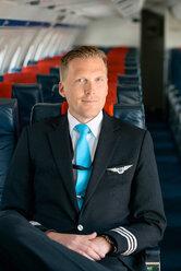 Portrait of smiling pilot sitting in passenger cabin - MASF00018