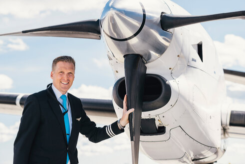 Portrait of smiling pilot standing by airplane's propeller at airport - MASF00021