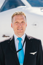 Portrait of confident male pilot standing against airplane at airport on sunny day - MASF00024