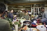 Multi-ethnic volunteers examining textiles in warehouse - MASF00036
