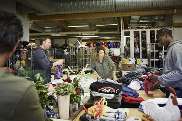 Multi-ethnic volunteers examining textiles in warehouse - MASF00036
