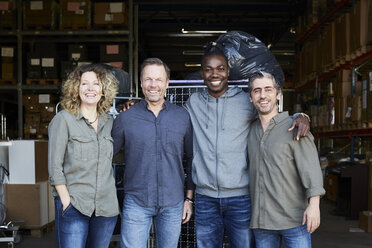 Portrait of smiling colleagues standing at warehouse doorway - MASF00045