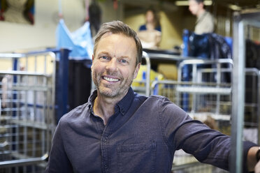 Portrait of smiling mature man standing in illuminated warehouse - MASF00054