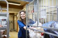 Smiling mature female volunteer pushing cart while looking away at warehouse - MASF00060