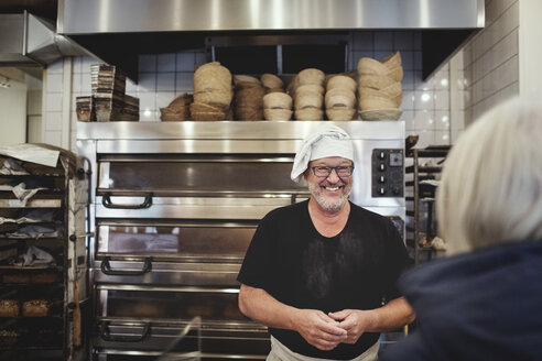 Smiling senior male baker standing against cooling rack at bakery - MASF00084
