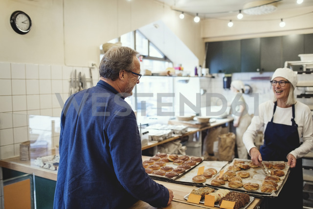 Smiling female owner showing fresh baked food to customer at bakery - MASF00093