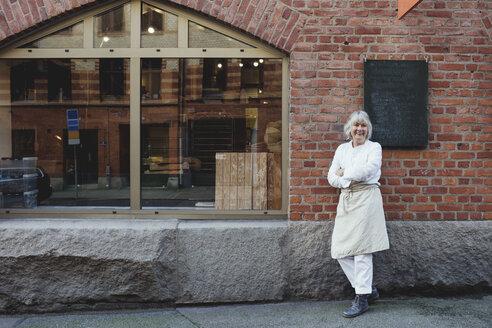 Full length of smiling baker standing on sidewalk against brick wall - MASF00096