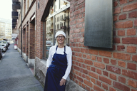 Portrait of smiling baker leaning on brick wall outside bakery - MASF00099