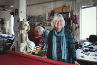 Portrait of smiling senior female standing at workbench in workshop - MASF00108