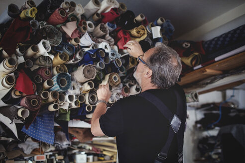 Low angle view of senior male owner looking at rolled fabrics in workshop - MASF00114