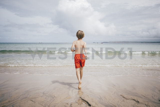 Rear view of shirtless boy walking on shore at beach against sky - MASF00135