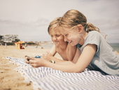 Happy siblings sharing smart phone while lying on towel at beach against sky - MASF00138