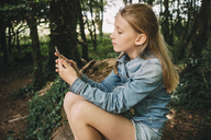 Side view of blond girl using smart phone in forest - MASF00141