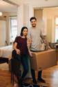 Portrait of smiling couple standing with box by rooms at home - MASF00147