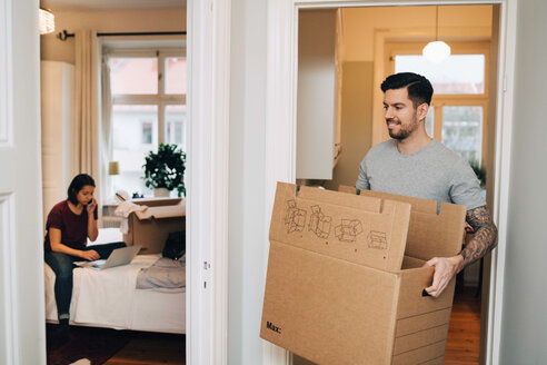 Smiling man carrying box from doorway towards woman using laptop in bedroom - MASF00150