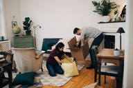 Couple unpacking boxes together in living room at new home - MASF00153