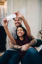Smiling couple taking selfie on mobile phone while resting on bed in bedroom - MASF00156