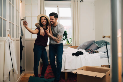 Smiling couple taking selfie on mobile phone while standing in bedroom - MASF00162