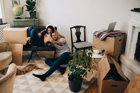 Smiling couple video calling through mobile phone while sitting in living room during relocation - MASF00177