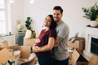Smiling man embracing pregnant woman while standing against boxes in living room - MASF00180
