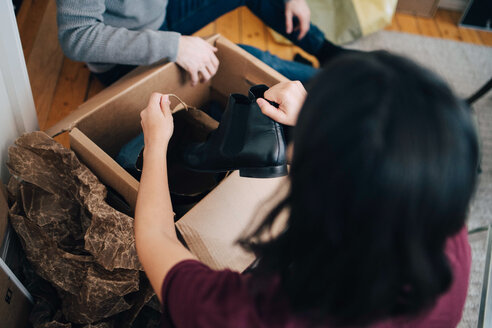 Woman removing shoe from box while sitting with man in apartment - MASF00195