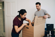 Man assisting woman in unpacking box at new house - MASF00198