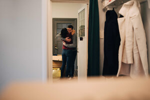 Couple embracing seen from doorway in new apartment - MASF00204