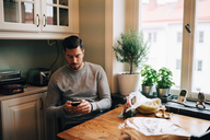 Man using mobile phone while sitting at table in kitchen - MASF00207