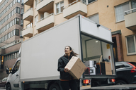 Woman carrying box while standing by delivery van in city - MASF00249
