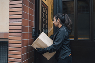 Female messenger ringing intercom while carrying box by closed door - MASF00255