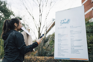 Female worker carrying box and document with smart phone looking at billboard - MASF00267