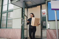 Smiling female worker with box using mobile phone while coming out of building - MASF00270