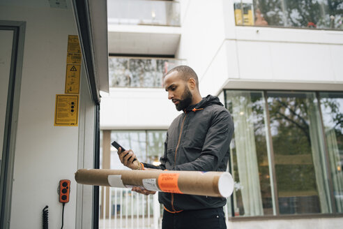 Male messenger with package using mobile phone while standing by delivery van - MASF00276