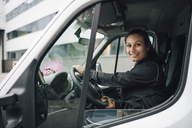 Portrait of smiling woman driving delivery van in city - MASF00285
