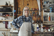 Portrait of smiling senior owner standing against tools at workshop - MASF00297