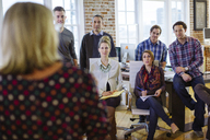 Business people listening to businesswoman explaining in meeting at office - CAVF34454