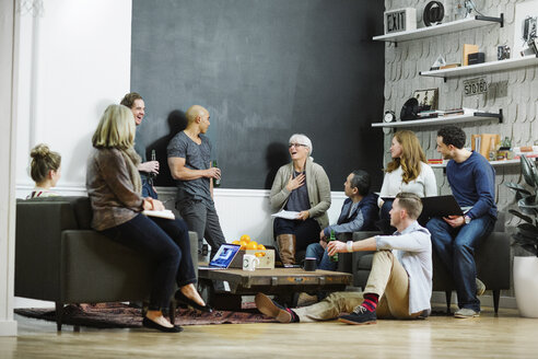 Business people discussing while relaxing in office - CAVF34472