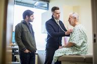 Male doctors examining patient sitting on bed in hospital ward seen through doorway - CAVF34541