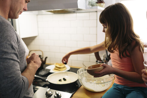 Father and daughter preparing food in kitchen at home - CAVF34625
