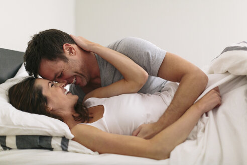 Close-up of smiling couple in bed at home - CAVF34634