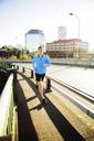 Full length of man jogging on footpath in city - CAVF34670