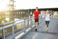 Friends jogging together on bridge against clear sky - CAVF34676